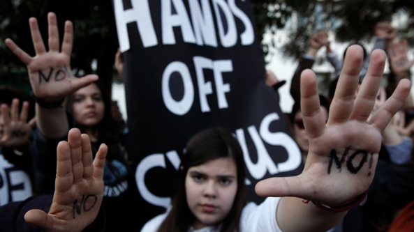 "Protesters raise their open palms showing the word ""No"" during an anti-bailout rally in Nicosia"